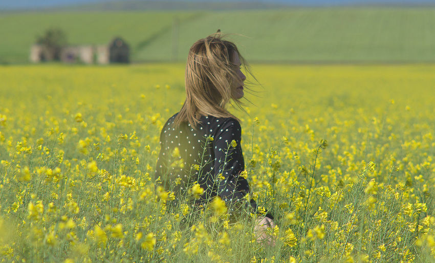 Rear view of woman amidst yellow flowers on field