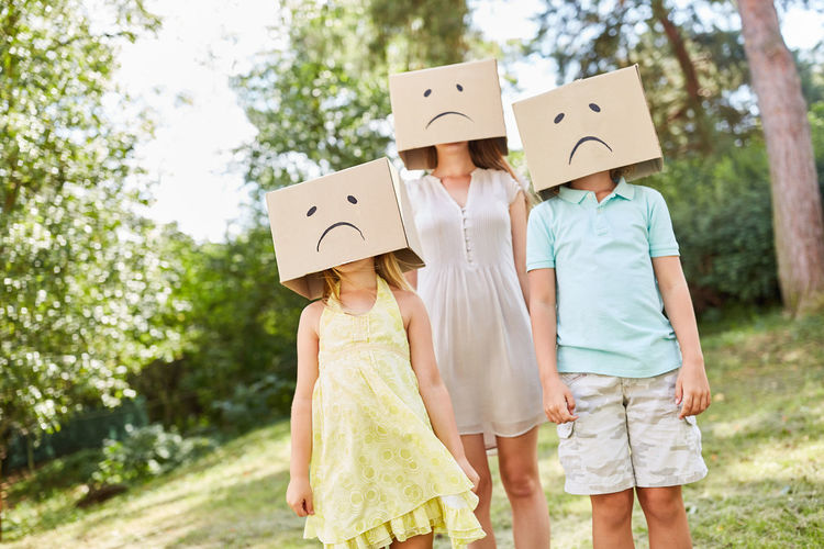 Woman with children wearing cardboard boxes while standing in park