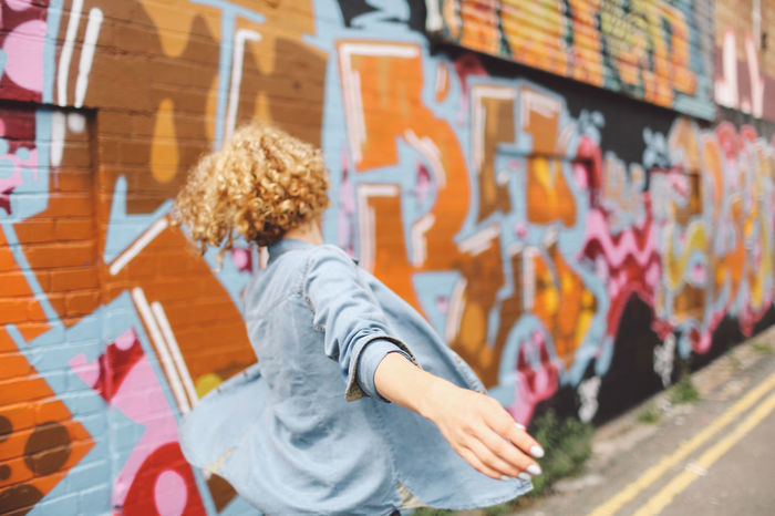 Blonde Brighton Casual Clothing City Life Curly Hair Day Focus On Foreground Girl Graffiti Graffiti Art Joyful Jumping Leisure Activity Lifestyles Multi Colored Playful Selective Focus Spinning People And Places