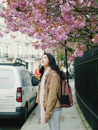 Woman standing by pink flower in city