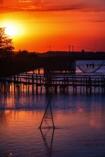 Silhouette pier on water against orange sky