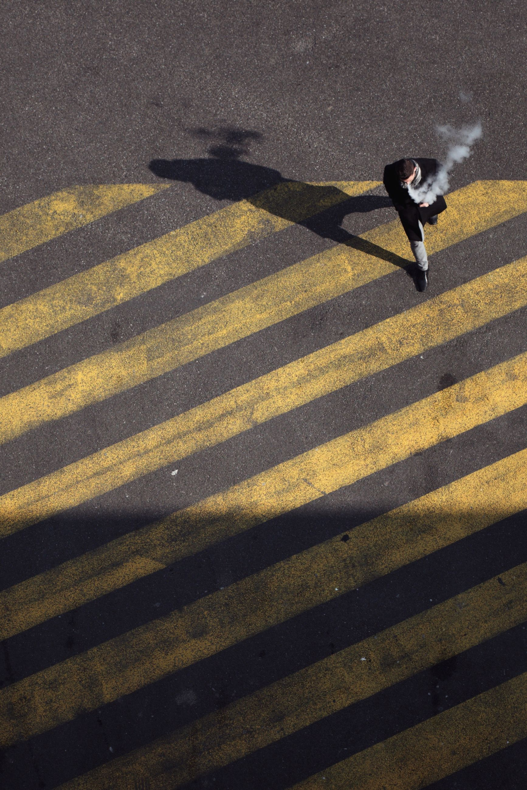 shadow, one person, full length, road, city, nature, sunlight, transportation, street, sign, motion, high angle view, day, road marking, yellow, outdoors, real people, adult, lifestyles, focus on shadow