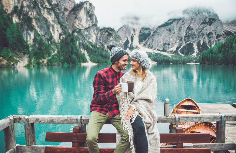 Couple sitting on mountain by lake against mountains