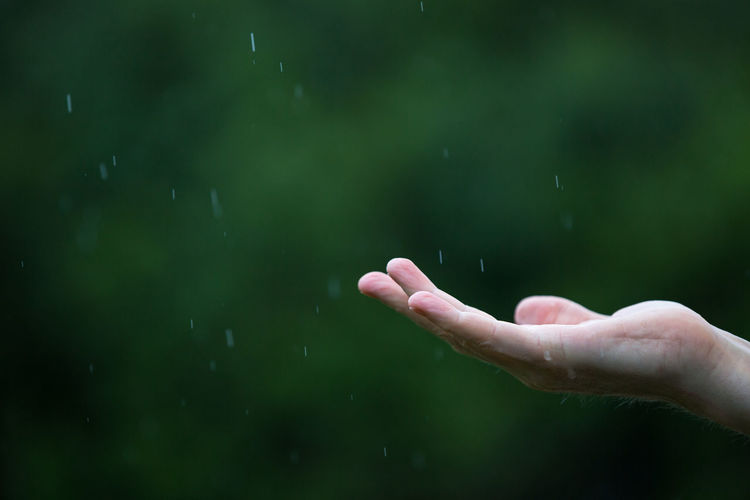 Cropped image of person with raindrops falling on hand