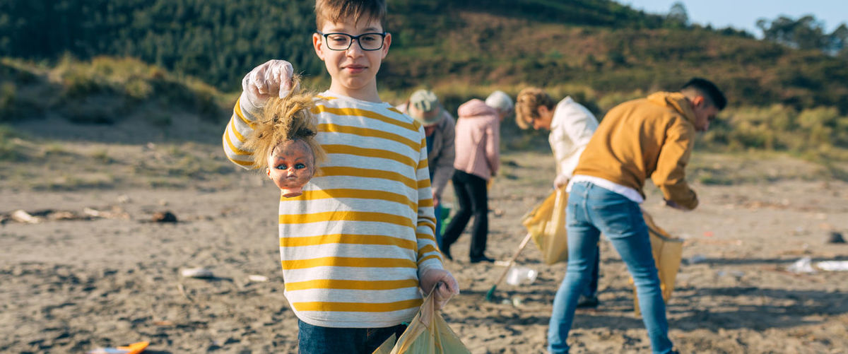 Portrait of boy holding garbage while standing at beach