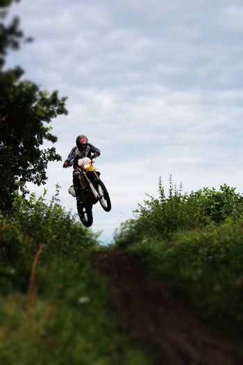 Low angle view of motocross racer performing stunt over dirt road against sky