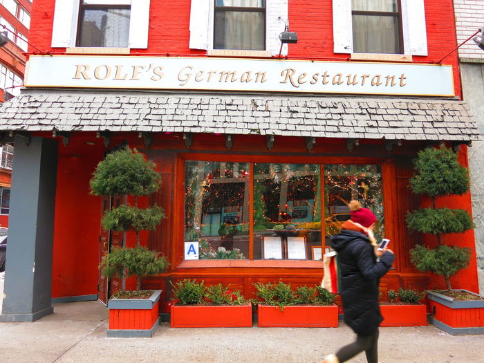 New York City - 21 February 2015: A woman looks at her smartphone as she walks passed Rolf's German Restaurant in Manhattan on a cold day. Famous for its Black Forrest Christmas decor. Adults Only Architecture Bar Building Exterior City Day Exterior Exterior Building Faa Famous Place Food And Drink German Restaurant Lifestyle New York City NYC Street One Person One Woman Only Only Women Outdoors Pub Restaurants Rolf Rolf's German Restaurant Warm Clothing Women