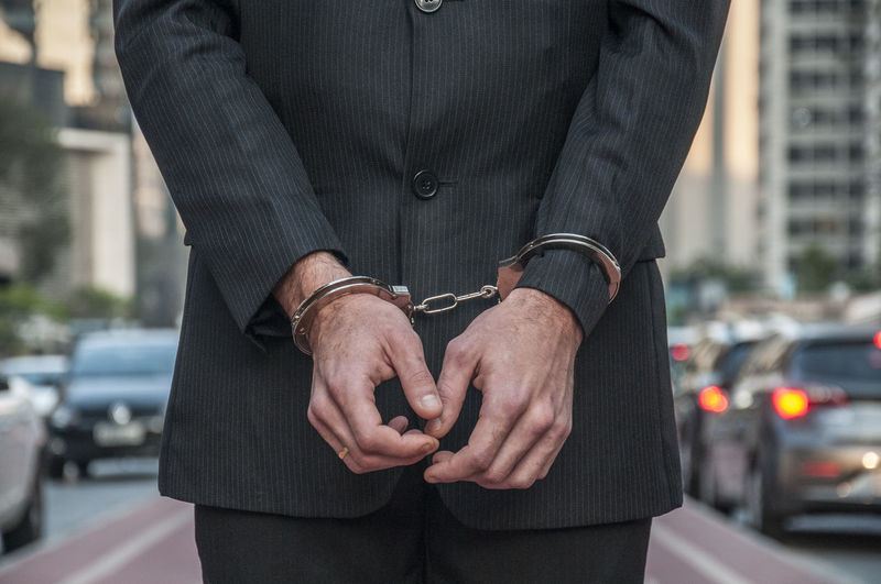 Midsection of businessman wearing handcuff on street in city