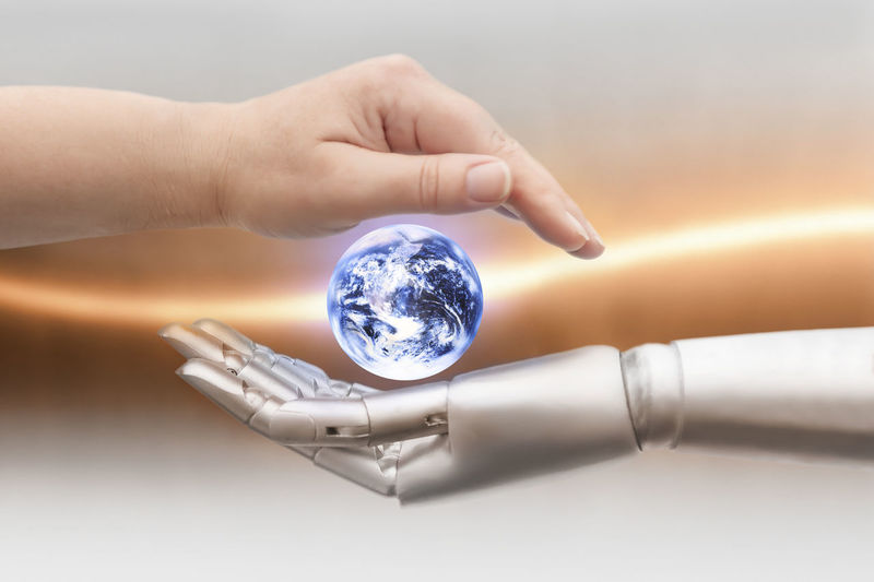 Close-up of robot and human hands covering globe