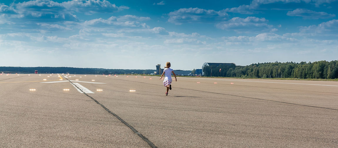 Rear View Full Length Of Girl Running At Airport Runway
