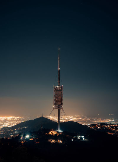 Communications tower against sky at night
