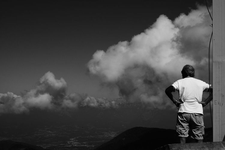 Rear view of man standing by sea against cloudy sky