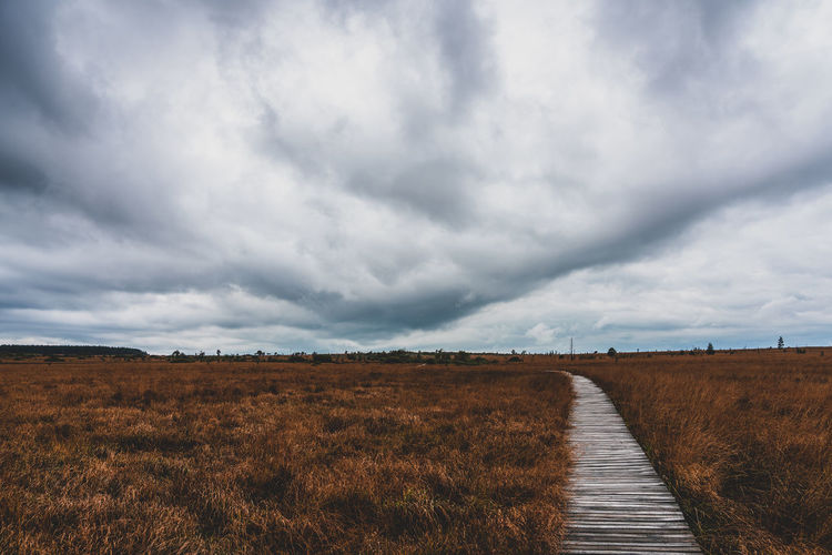 View of footpath in field against cloudy sky