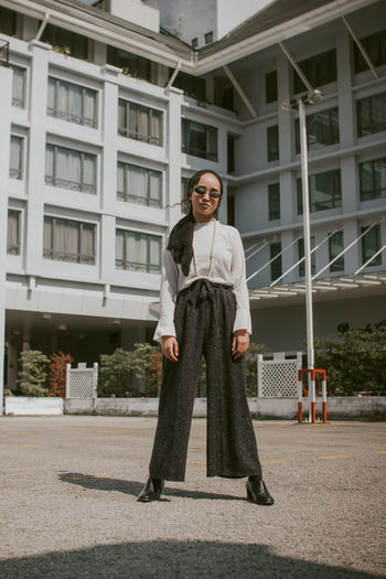 Portrait of woman wearing sunglasses standing against building