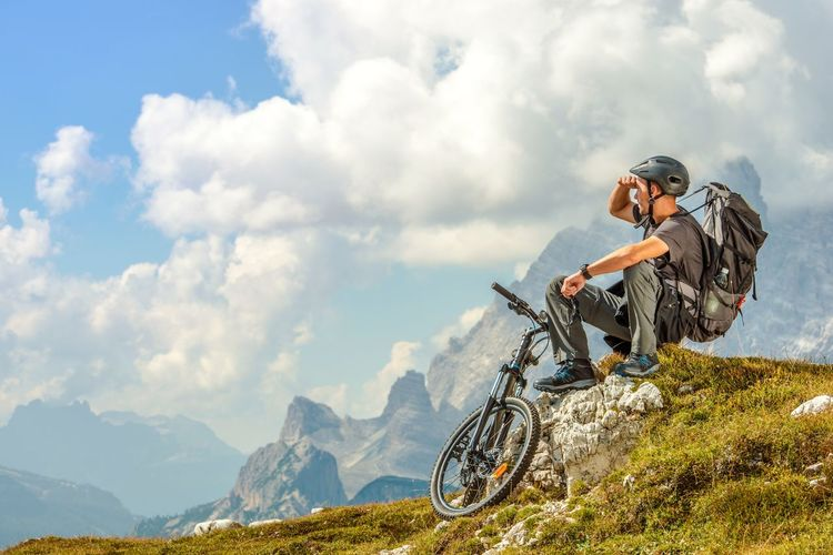 Man sitting with bicycle on mountain against cloudy sky
