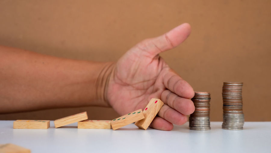 Cropped image of hand holding coins on table