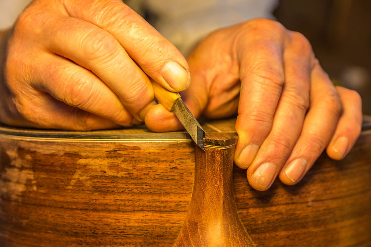 Cropped Hands Of Man Carving On Wood