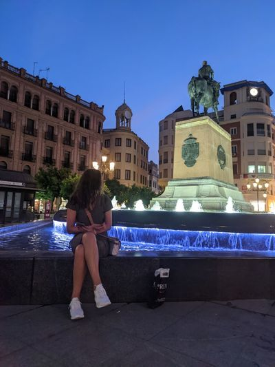 Woman sitting on illuminated building against blue sky in city