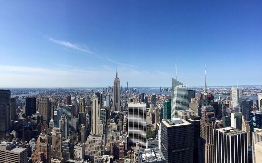 Manhattan against blue sky on sunny day
