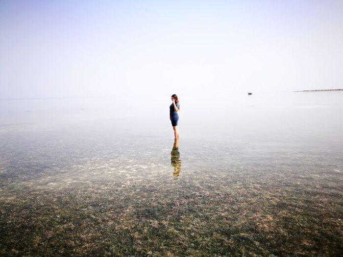 Teenage girl standing in sea against sky
