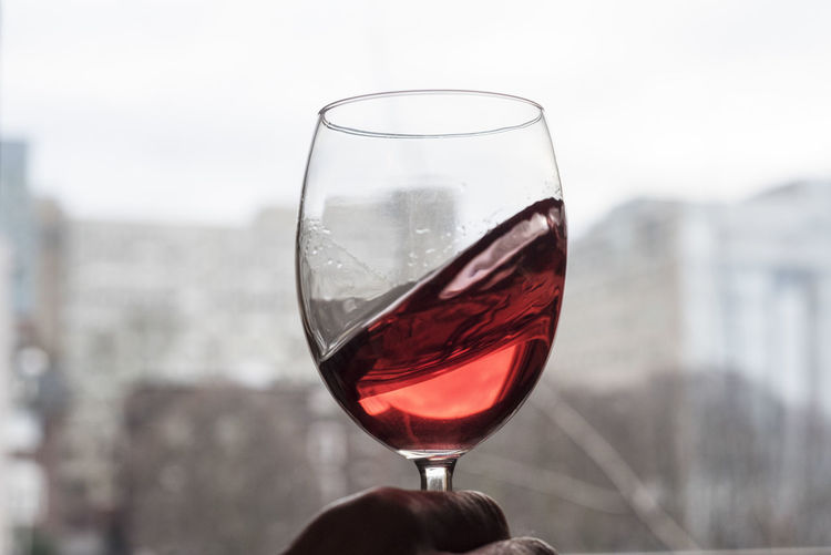 Cropped Hand Of Man Swirling Wineglass Against Window