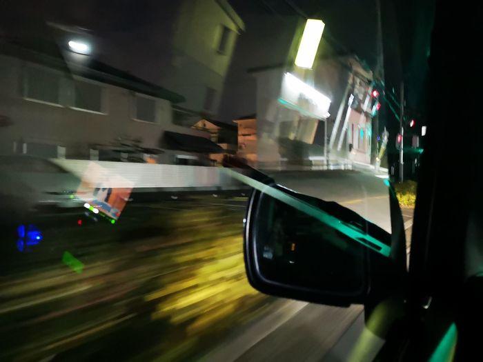 Blurred motion of car on illuminated street at night