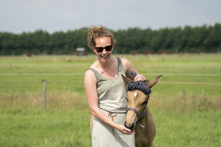 Smiling woman with horse on field