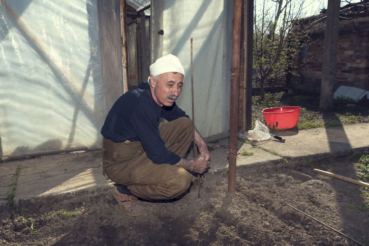 Caucasian man planting onion sets Agriculture Crouching Gardening Growing Growth Land Lines Planting Rural Set Sunny Bulb Caucasian Cultivated Land Day Dirt Farming Garden Greenhouse Mustache One Man Only Onion Soil Springtime Yard