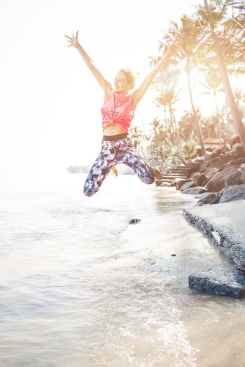 Happy Woman Jumping At Beach Against Sky