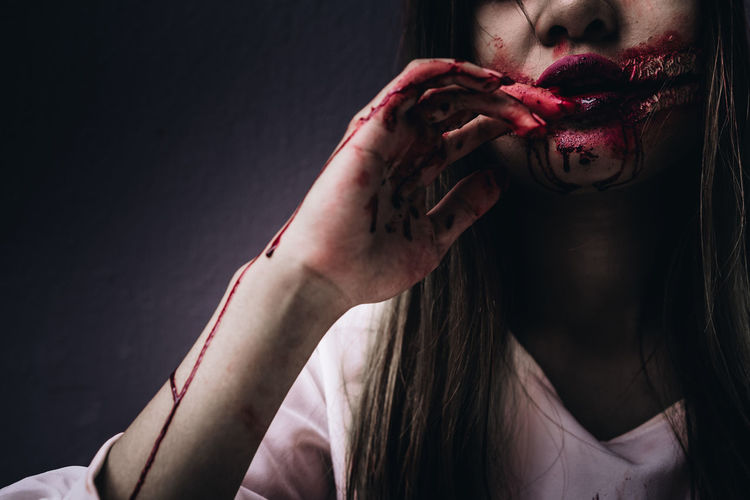 Midsection Of Young Woman With Halloween Make-Up Against Wall