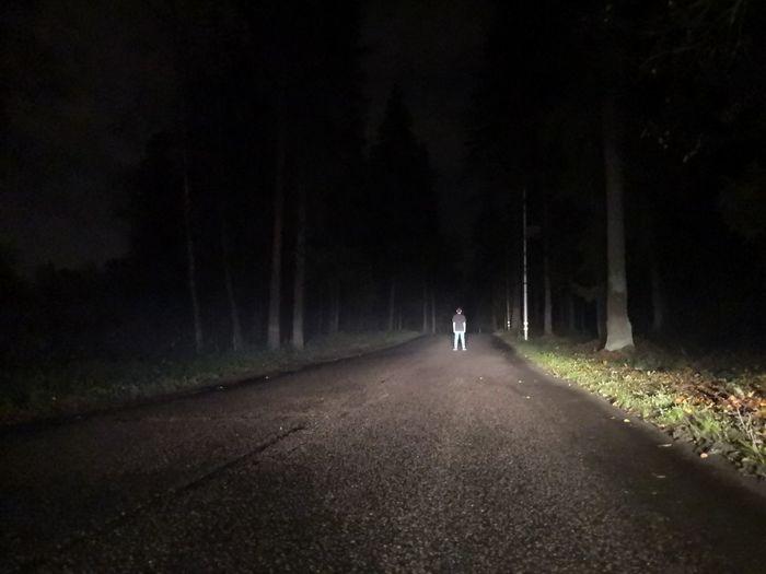 Rear view of man walking on road along trees at night