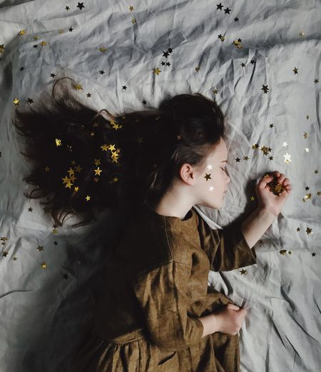 Sleeping child with stars in her hair Bed Casual Clothing Child Childhood Directly Above Flower Flowering Plant Front View Hairstyle High Angle View Indoors  Leisure Activity Lifestyles Magic One Person Portrait Real People Stars Waist Up