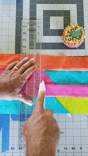 Close-up of hand cutting multi colored paper with utility knife