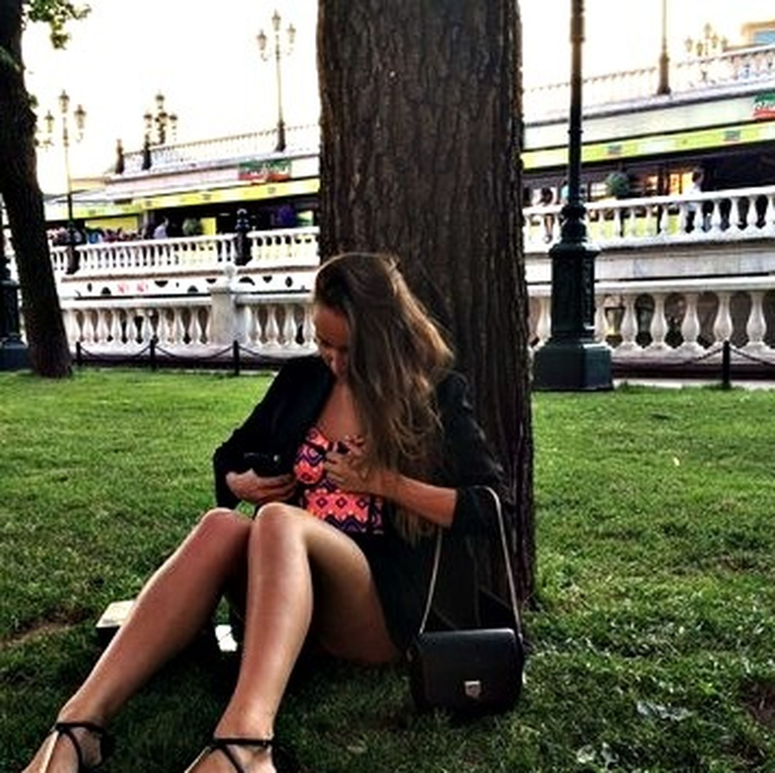 lifestyles, young adult, leisure activity, young women, casual clothing, person, sitting, grass, holding, side view, three quarter length, tree, long hair, communication, transportation, photography themes, wireless technology
