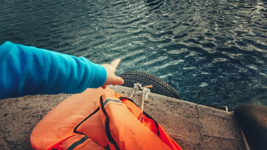 View of person pointing at rippled water