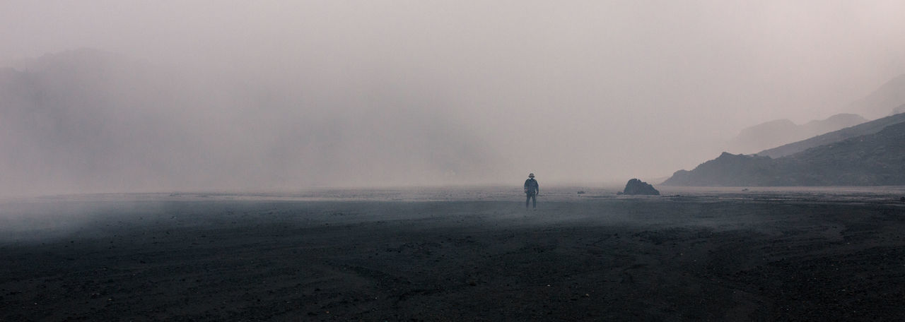 Man Standing On Landscape Against Sky During Foggy Weather