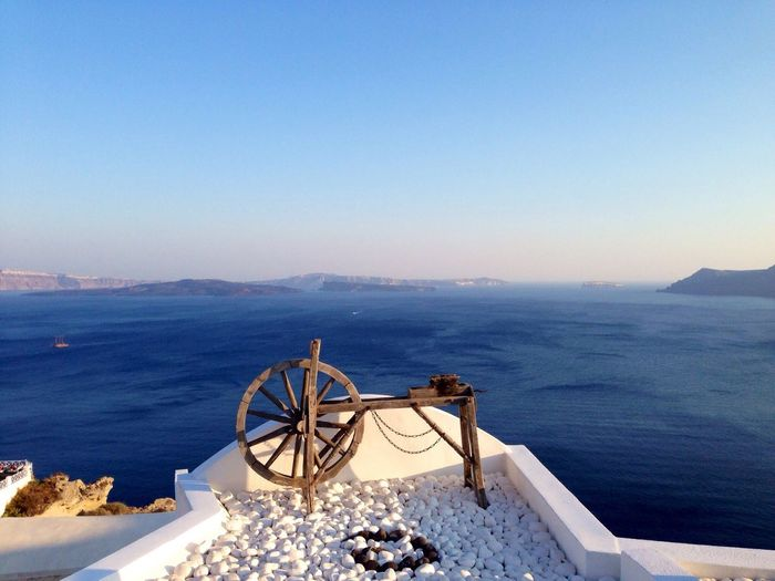 Wooden wheel on top of house against river in santorini