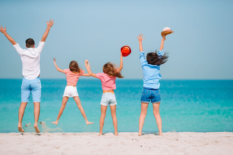 Rear view of family jumping at beach