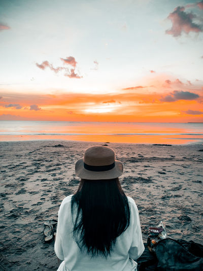 Rear view of woman in sea against sky during sunset