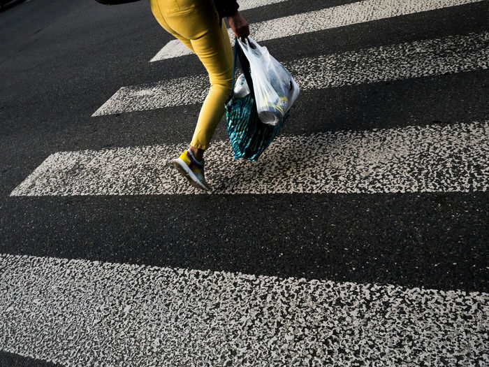 Low section of woman carrying shopping bags on zebra crossing