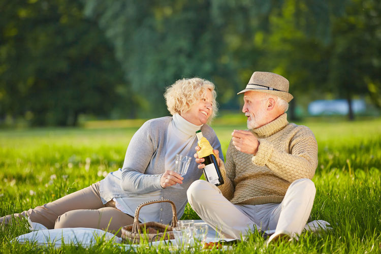 Senior Couple With Wineglass And Bottle Sitting On Field