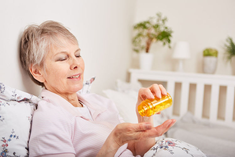 Woman looking away while sitting on bed