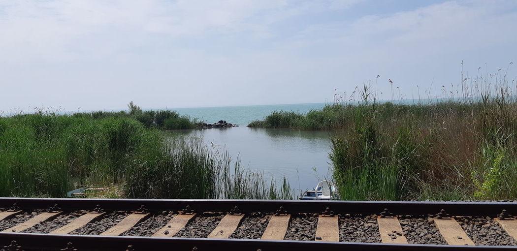 Railroad tracks by lake against sky