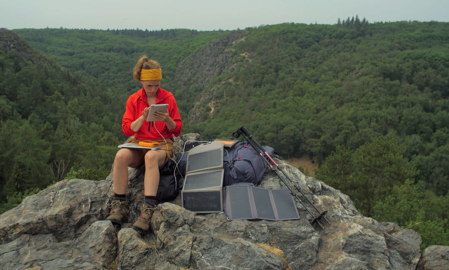 caucasian female hiker sitting on a rock while working on a laptop being charged by solar panels nearby, portable solar charing technology concept Backpacking Camping Charing Cross Freedom Hiking Nature Sitting Solar Panel Tablet Travel Trekking Woman Working Adventure Battery Beauty In Nature Casual Clothing Connection Day Female Full Length Hiking Internet Laptop Leisure Activity Lifestyles Mountain Nature Navigation One Person Outdoors People Plant Portable Information Device Real People Rock Rock - Object Sitting Solid Technology Tree Young Adult