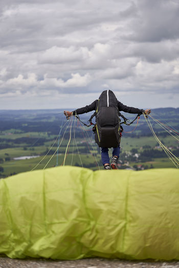 Man paragliding from mountain against sky