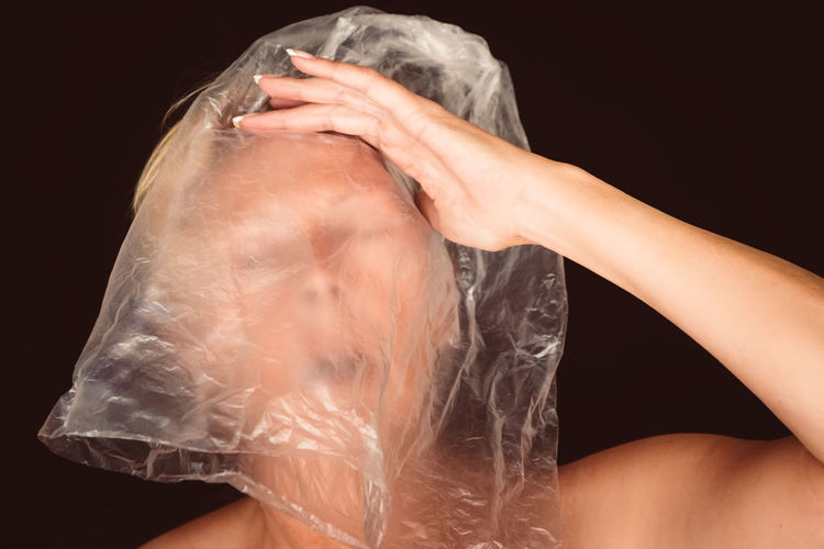 Shirtless woman covering face with plastic bag against black background
