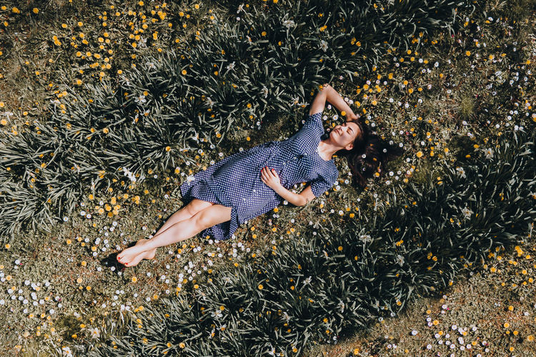 High angle view of woman lying down on field with flowers