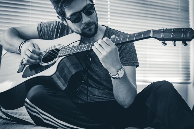 Man playing guitar while sitting on bed at home