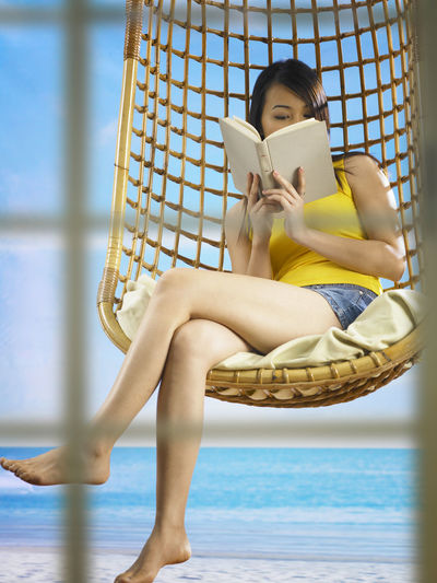 woman reading book on the swing Asian  Free Time On The Swing Reading Woman Book Boredom Concentrate Concentration Leisure Leisure Activity Lying Backwards Novel One Person One Woman Only Outdoors Outdoors Photograpghy  Portrait Reading A Book Relax Sky Study Swing Swings