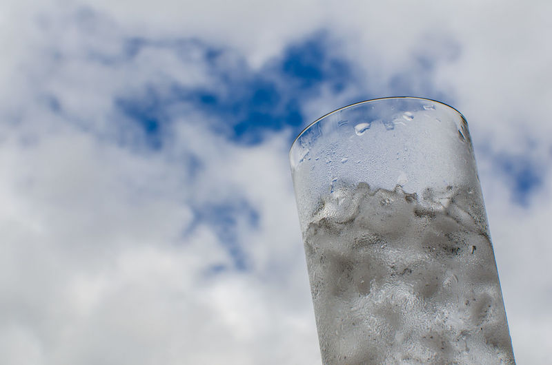 Low Angle View Of Glass With Ice Cubes Against Cloudy Sky